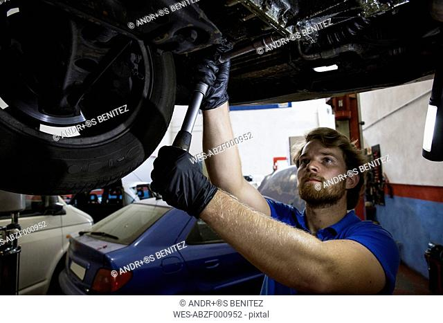 Mechanic fixing suspended car in his workshop