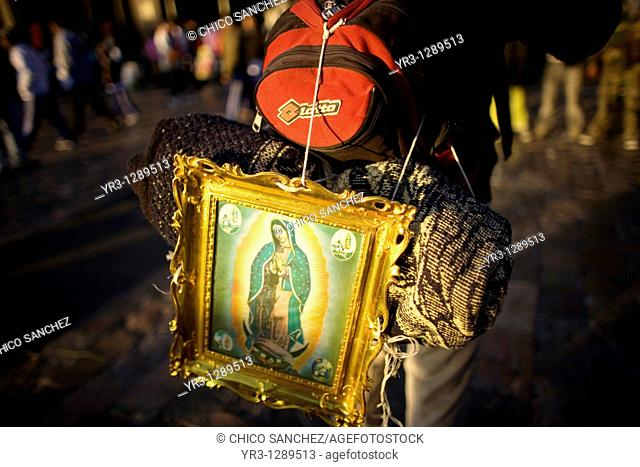 A pilgrim carries on his back an image of the Our Lady of Guadalupe outside of the Our Lady of Guadalupe Basilica in Mexico City, December 11