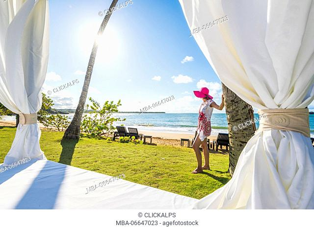Playa Moron, Las Terrenas, Samana Peninsula, Dominican Republic. Beautiful woman admiring the view from by a beach bed (MR)