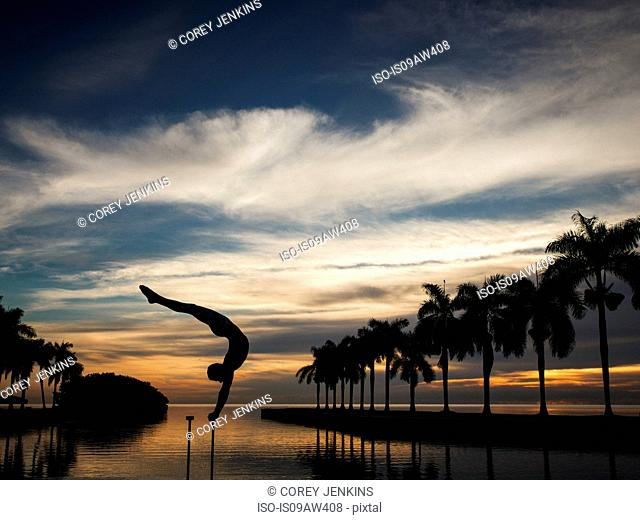 Mature man balancing on pole in water, dusk, South Pointe Park, South Beach, Miami, Florida, USA