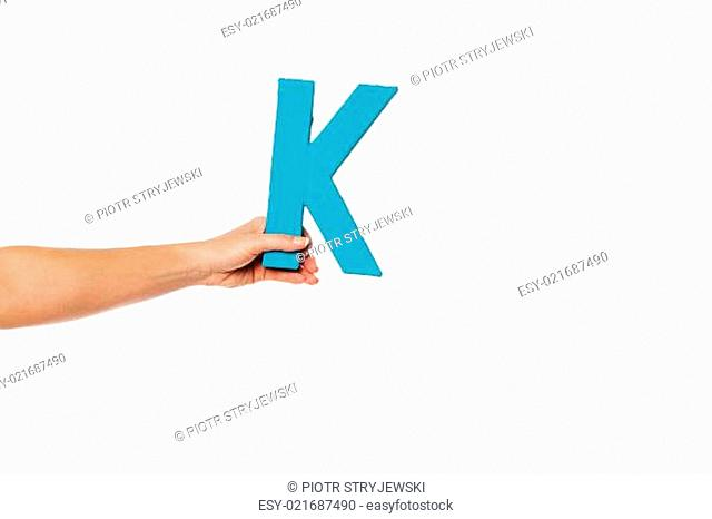 hand holding up the letter K from the left