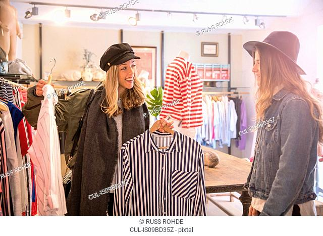 Two female friends, looking at clothes in shop
