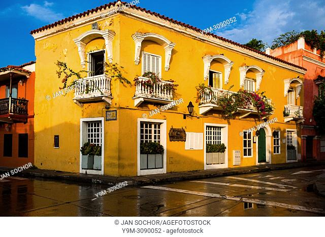 A Spanish colonial house, decorated with flowers, is seen reflected on the pavement in the walled city of Cartagena, Colombia, 12 December 2017