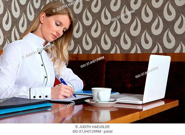 Woman studying with laptop in cafe
