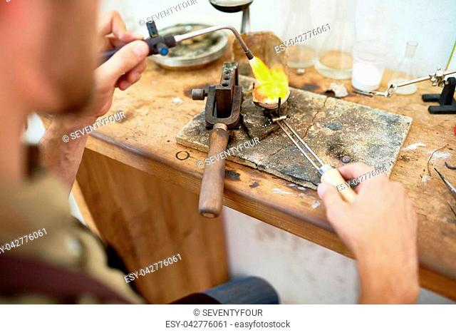 Closeup portrait of jeweler melting precious metal ring on working table with different tools