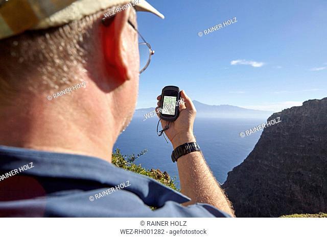Spain, Canary Islands, La Gomera, hiker using gps navigation device