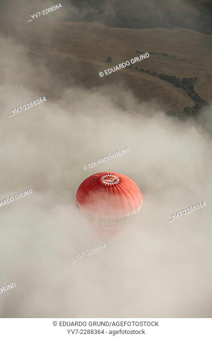Balloon crossing a cloud layer in European hot air balloon festival Igualada, Barcelona, Catalonia, Spain, Europe