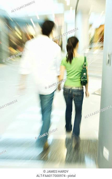 Couple walking in shopping mall, rear view, blurred motion