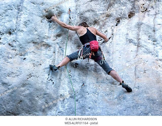 Thailand, Krabi, Chong Pli, woman climbing in rock wall