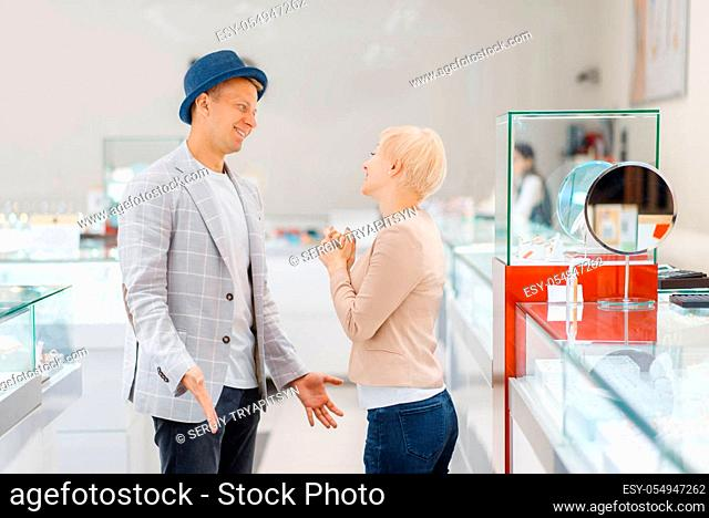Young Love couple buying jewels in jewelry store. Man and woman choosing wedding rings. Future bride and groom in jewellery shop
