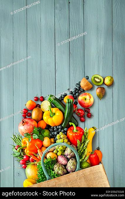 Fruits and vegetables and beige canvas bag with blue handle sitting on top of rustic wood table background