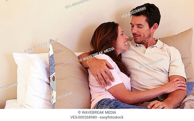 Happy couple cuddling on bed and chatting