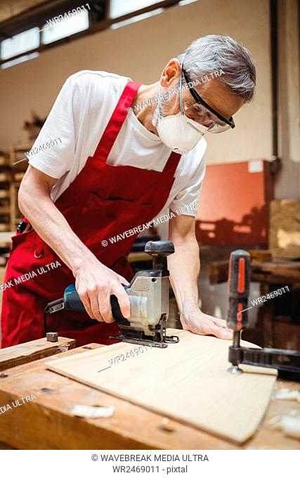 Carpenter cutting a plank of wood in carpentry