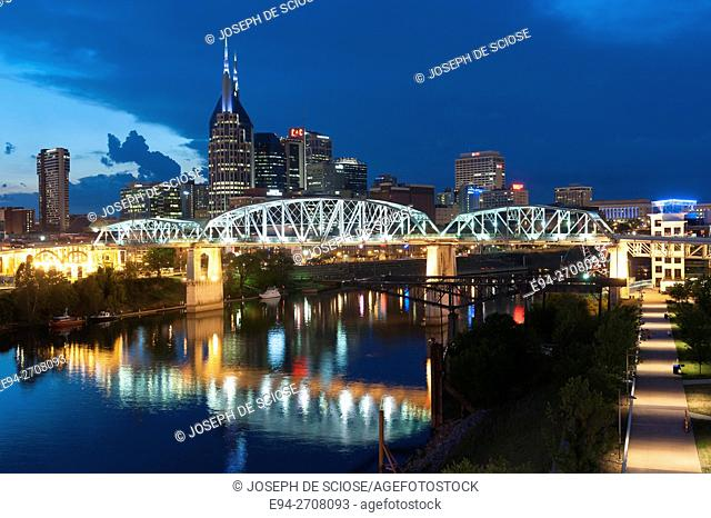 Twilight view of the Nashville Tennessee skyline with the Cumberland River and the Shelby Street Bridge in the foreground