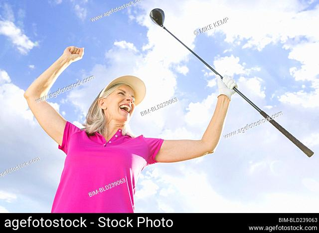 Caucasian woman celebrating with golf club