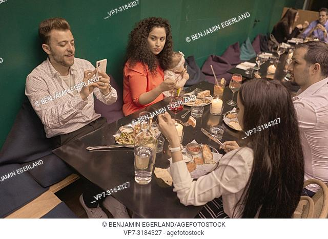Family eating in restaurant, phone, man using smartphone, Vegan Oriental, Kismet, in Munich, Germany