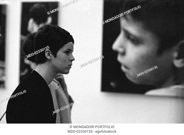 A young woman visiting the biennial fair dedicated to photography. Cologno Monzese, 1966