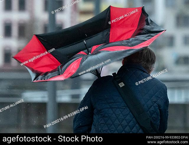 dpatop - 16 February 2020, North Rhine-Westphalia, Dortmund: The umbrella of a walker is folded down at Lake Phoenix because of a gust of wind