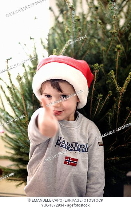 Child with Santa Claus hat makes hand gesture thumb up