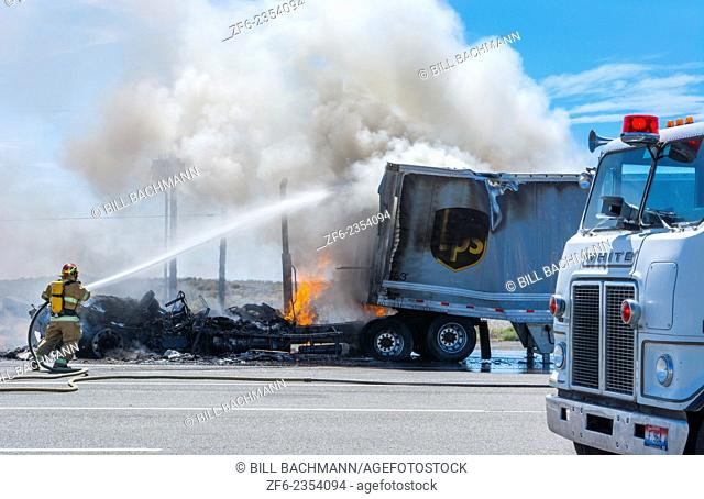 Emergency fire of truck on road in Idaho near Twin Falls Idaho with firefighters and hose putting big flames and smoke out danger hot first responders