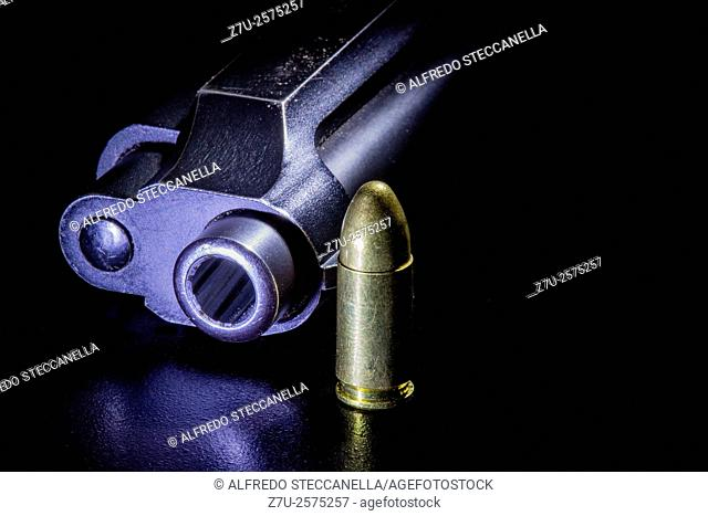 Black gun and bullets on a black background
