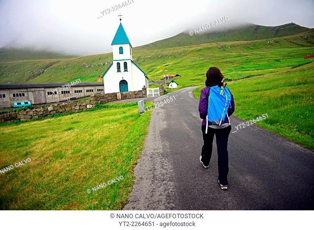 Young woman walking around the village of Gjógv, Eysturoy, Faroe Island