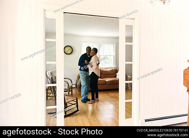 Senior couple dancing together in the living room and bonding