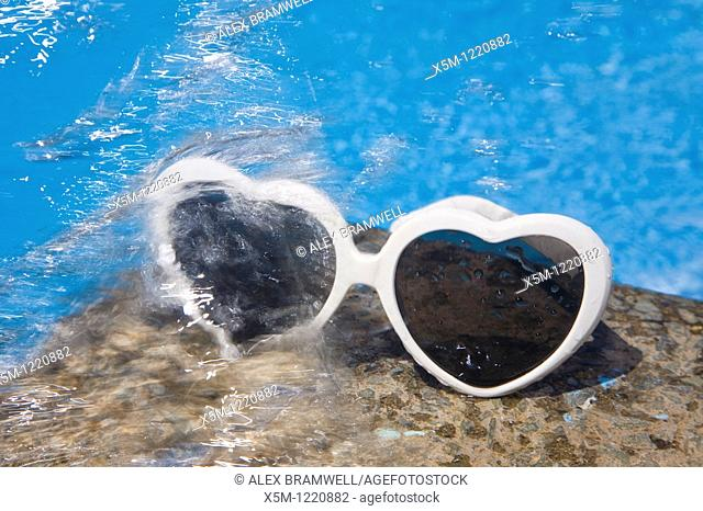Heart shaped sunglasses by a bright blur swimming pool with splashing water