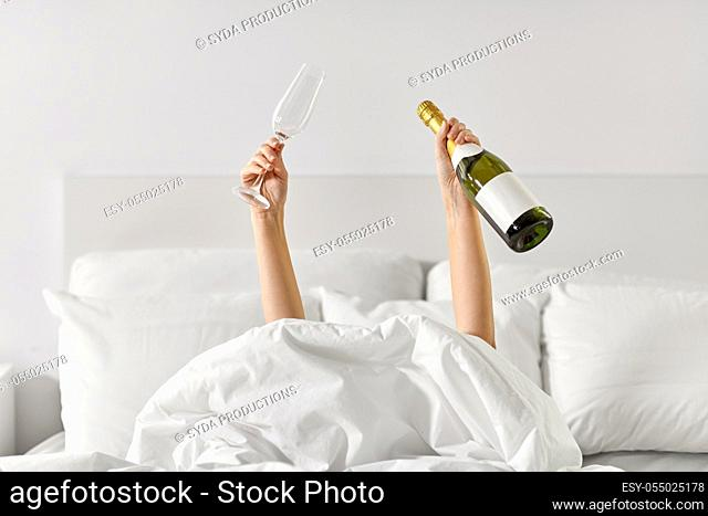 hands of woman lying in bed with champagne