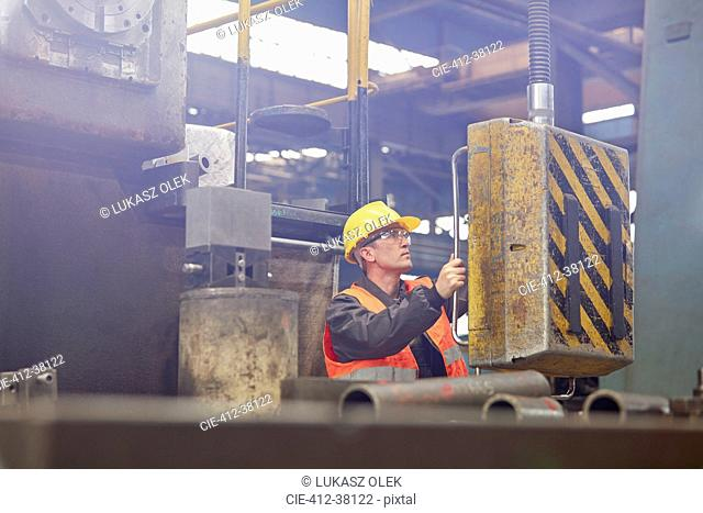 Male worker operating machinery in factory