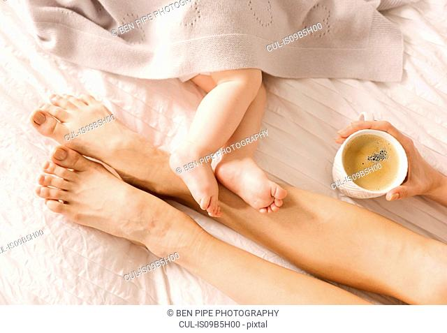 Mother and baby's bare feet on each other on bed