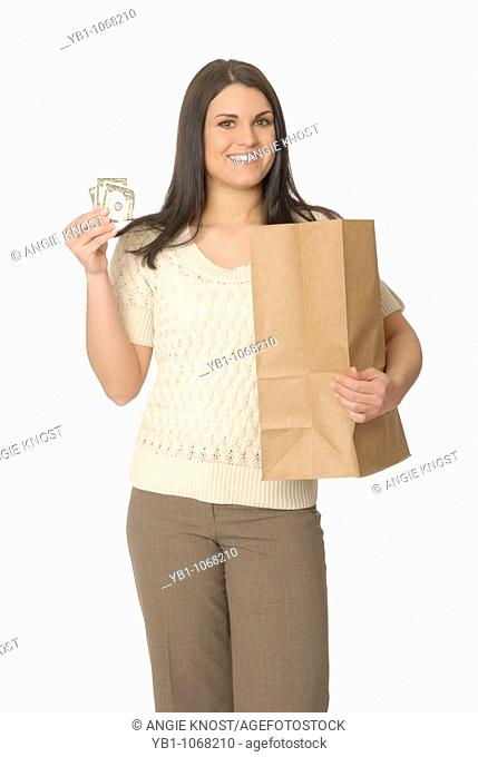 Attractive woman with a brown paper shopping bag and money