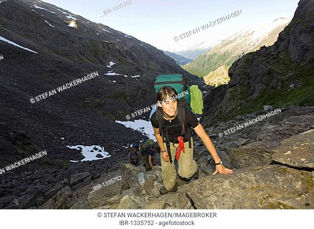 Young woman hiking up, backpacking, hiker, legendary Golden Stairs of Chilkoot Trail, Chilkoot Pass, view into Taiya River Valley