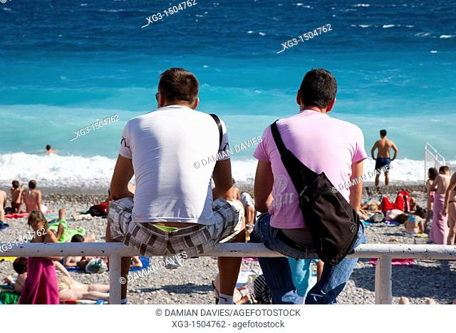 Two men sit and watch the beach life beside the Promenade des Anglais, Nice, Provence, France