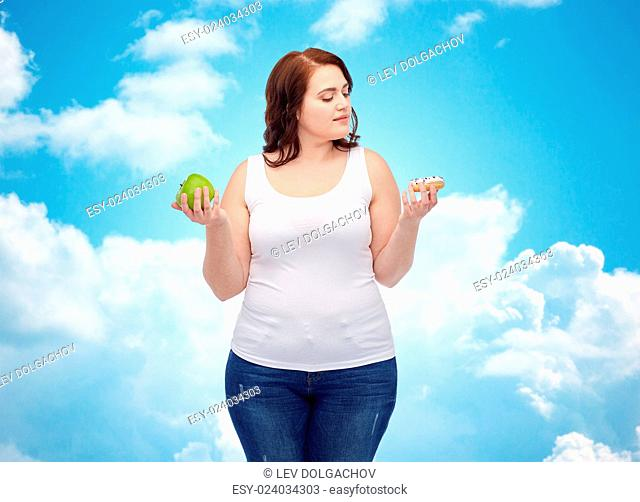 healthy eating, junk food, diet and choice people concept - plus size woman choosing between apple and cookie over blue sky and clouds background