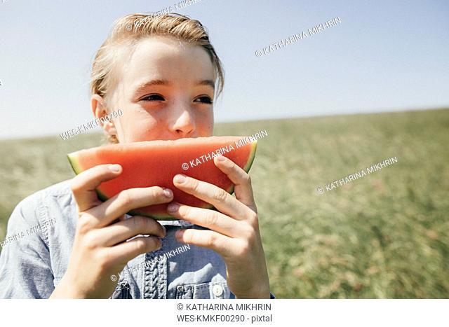 Boy on a field eating a watermelon