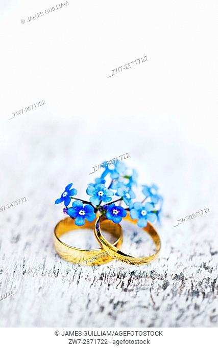 Two gold wedding rings his and hers with forget me not flowers