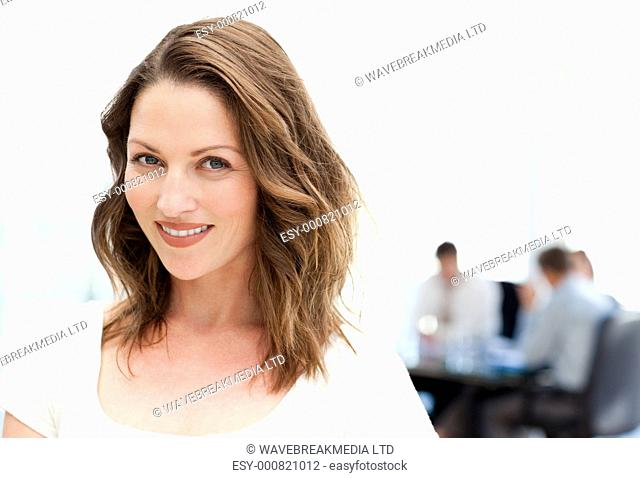 Relaxed businesswoman standing in front of her team while working at a table