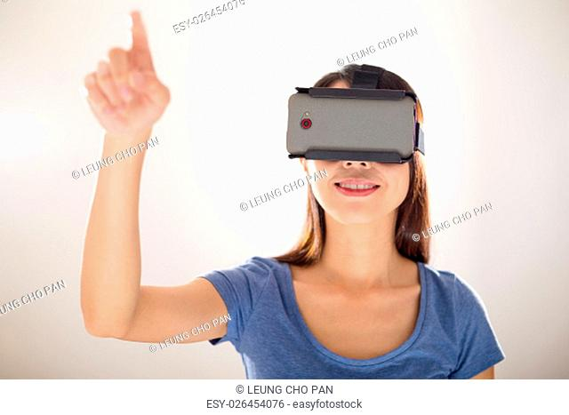Woman wearing virtual reality device and finger point up