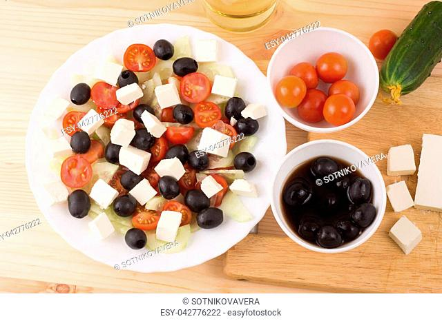Greek salad with vegetables, feta cheese, black olives in process. Wooden background . Top view