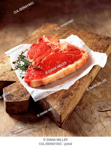 Food, meat, beef, t-bone steak, on rustic wooden chopping board