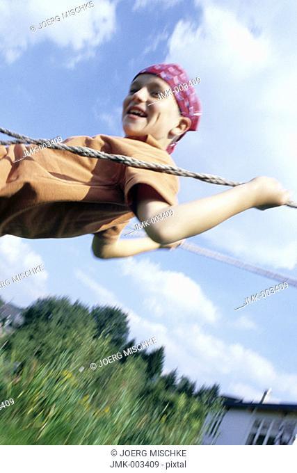 A boy, 5-10 years old, swinging outside in the garden in summer