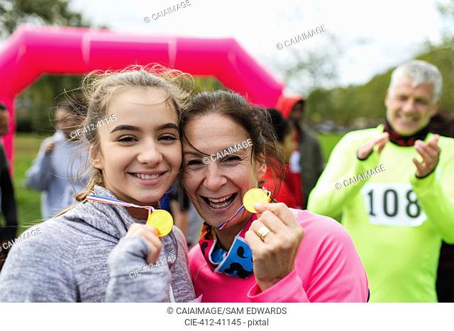 Portrait smiling, confident mother and daughter runners showing medals at charity run