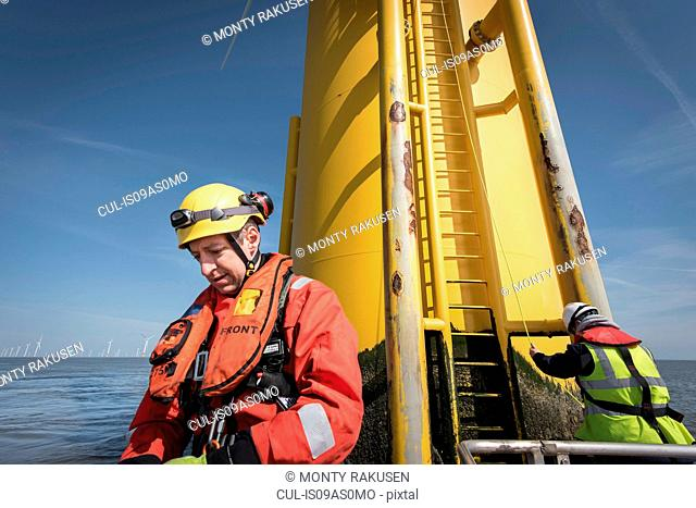 Engineer preparing to climb windturbine at offshore windfarm