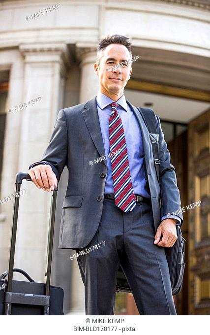 Mixed race businessman rolling luggage outdoors