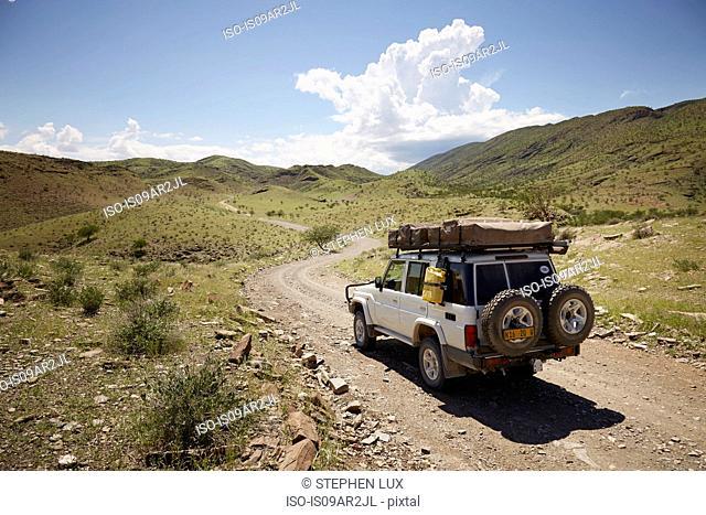 Off road vehicle on dirt path, rear view, Sesfontein, Kaokoland, Namibia