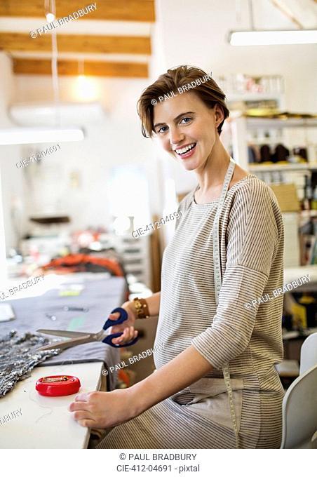 Dressmaker cutting fabric in studio