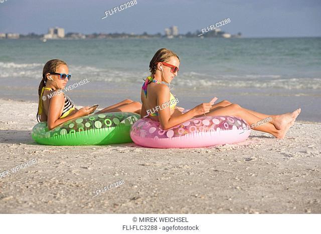 Girls on the beach relaxing on float toys, Sarasota, Florida, USA