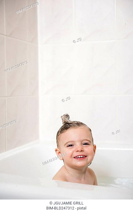 Smiling Caucasian girl in bubble bath