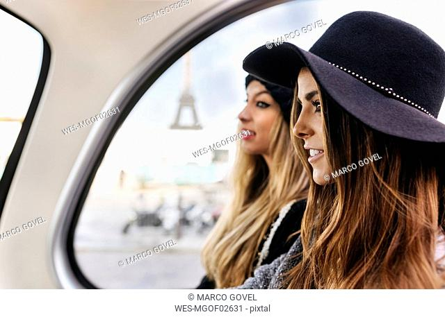 France, Paris, two women on a tour bus with the Eiffel Tower in the background